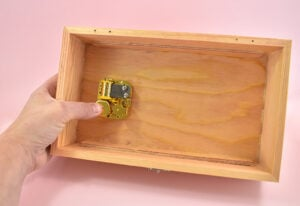 Place the mechanism inside of the jewelry box, aligning the screw holes.