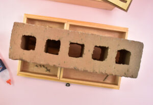If using a glue that takes a while to dry, it's advisable to place the interior trays onto the veneer to hold it down. Just make sure there isn't any glue on the top of the design, or squeezing out that will make the veneer glue to the bottom of the trays. Apply weight on top of the trays to help keep the smaller veneer pieces in place as the glue dries.