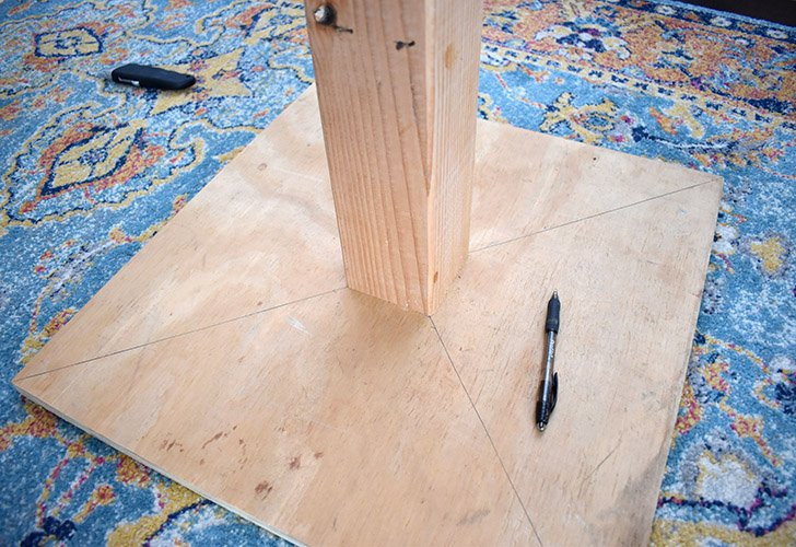 Using a straight edge (I used the post itself) draw a line from corner to corner to help easily locate the center of your plywood board. Place your 4x4 in the middle and trace its location.