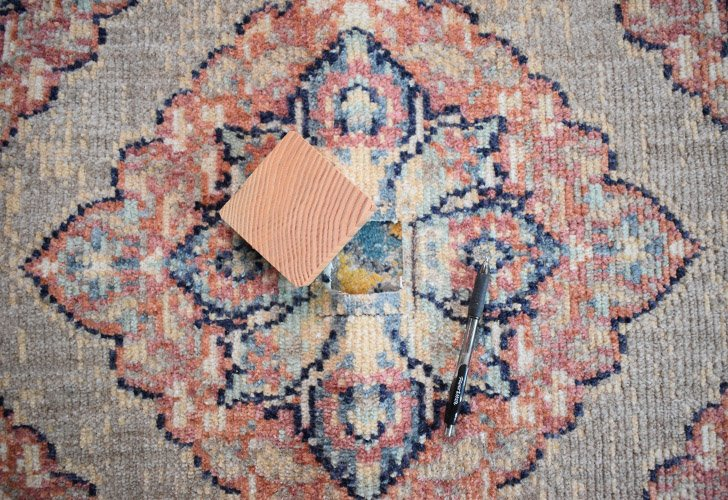 Mark the center of the rug you'll be covering the base with and draw out the shape of the 4 x 4 around the center.
