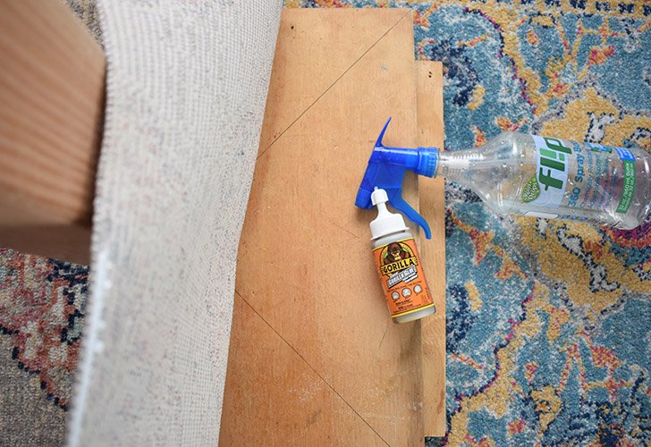 Pull the rug up from the base and apply a strong glue to affix.