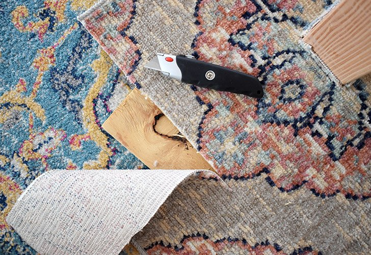 Use a utility knife with a sharp blade to carefully trim the excess carpet from the base.