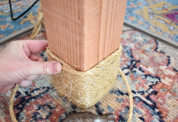 Using a small wire nail, tack the end of the rope onto the 4x4, over the rug stapled on.