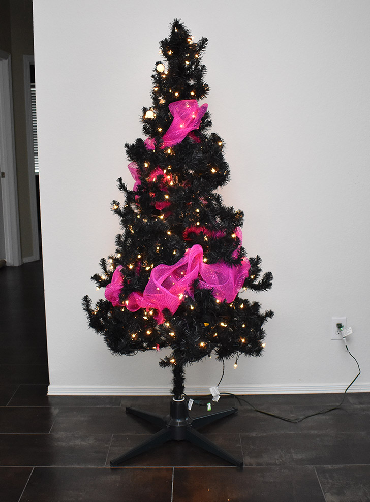 Plug in and run the hot pink LED lights through the tree and around. There is nothing perfect about the shape, you just need something that coils around the tree once or twice. Go over top of the lights with the hot pink deco mesh. Push it into the tree and bubble it out in other areas for an attractive look.