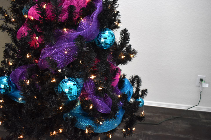 If adding disco ball ornaments place like colors with like or silver or gold ornaments around the black branches.