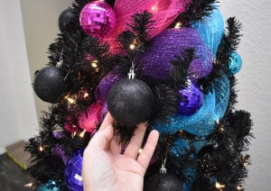 Place black ornaments around the black Christmas tree branches. These will sometimes block lights and help the tree twinkle as it turns.