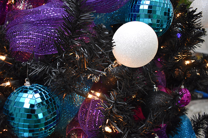 Next add your spring-y white globe ornaments. Use the clip to tuck the coil into the branches and stretch so that the ornament wiggles as the tree turns.