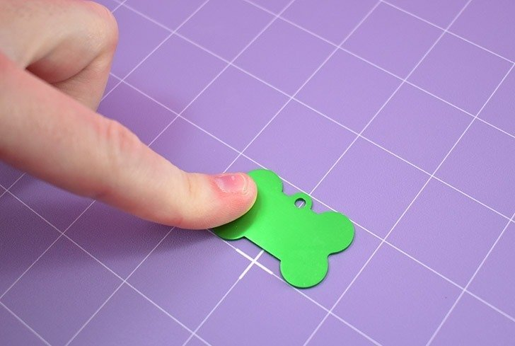 Press your aluminum dog tag firmly onto a StrongGrip mat to prepare for engraving.