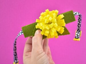 Begin applying the flowers where you please to the collar piece with hot glue.